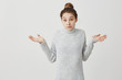 Caucasian woman throwing up hands with uncertainty on face. Female startup entrepreneur acting like have no idea or don't care over white background. Emotions concept