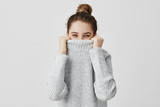 Cheerful facial expressions of woman looking from collar of her sweater with happy eyes. Content female with brown tied hair fooling around hiding her face in clothes. Fun and joy concept - 183214307