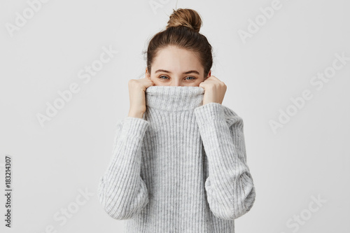 Cheerful facial expressions of woman looking from collar of her sweater with happy eyes. Content female with brown tied hair fooling around hiding her face in clothes. Fun and joy concept