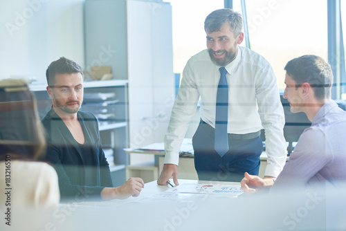 Fridge magnet Group of successful business people discussing work during meeting in office, focus on smiling bearded man talking to employees shot from behind glass door