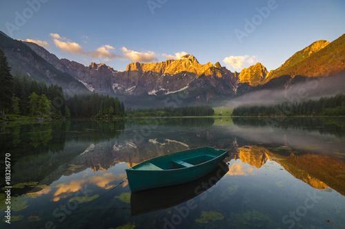 Fotobehang Zomer green boat on a mountain lake