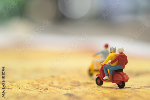Plexiglas Scooter Travel Concept. Group of traveler miniature figures ride motorcycle / scooter on world map.