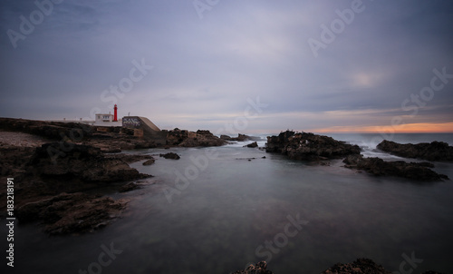 Long exposure from a lighthouse in a rocky beach in a cloudy winter day. Cascais, Portugal