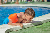 Cute Caucasian boy is getting out from the swimming pool through its side. - 183219701