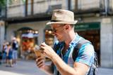 Short bearded man enjoying ice cream cone in a town street. - 183219747
