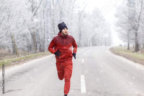 Plexiglas Fitness Young man running on a cold winter day.