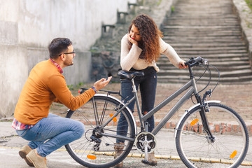 Happy young couple with a bicycle on sunny autumn day in the city.