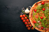 Pizza Primavera. Cherry tomatoes, arugula, cheese. On a wooden background. Top view. - 183224715