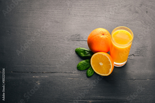 Poster Sap Orange fresh juice and oranges on a wooden surface. Top view. Free space for text.
