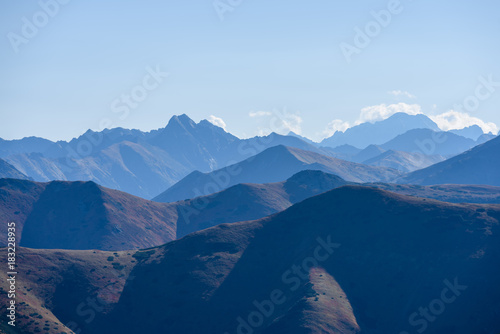 Foto op Aluminium Nachtblauw mountain tops in autumn covered in mist or clouds