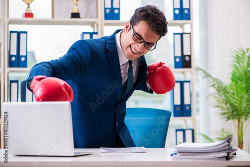 Businessman with boxing gloves angry in office