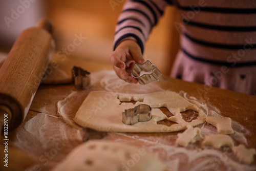 Sticker little girl in a kitchen making christmas cookies from a flour and fresh dough