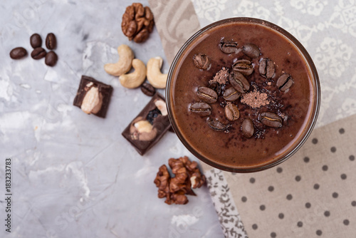 Foto op Aluminium Milkshake Chocolate smoothie on a glass with coffee beans and nuts on grey stone background