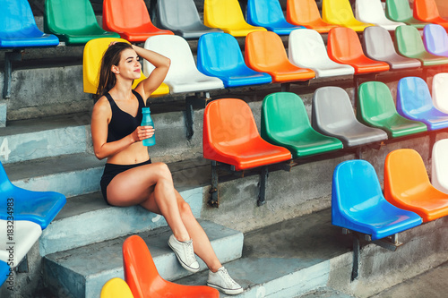 Cute sporty girl relaxing outdoor after training with bottle of water