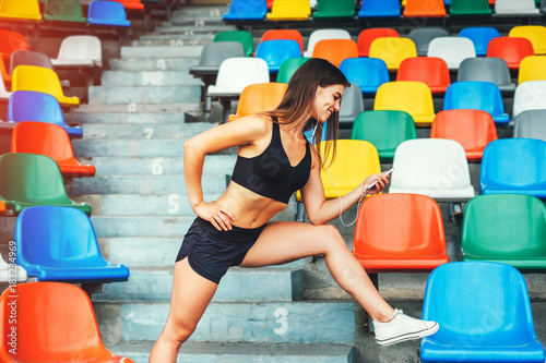 Cute young brunette sporty girl workout with phone outdoor Poster