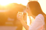 Happy lady holding a glass of water at sunset - 183247112