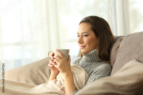 Foto op Canvas Wanddecoratie met eigen foto Tenant resting holding coffee on a couch