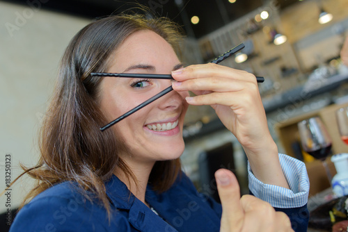 Woman holding chopsticks in front of her face