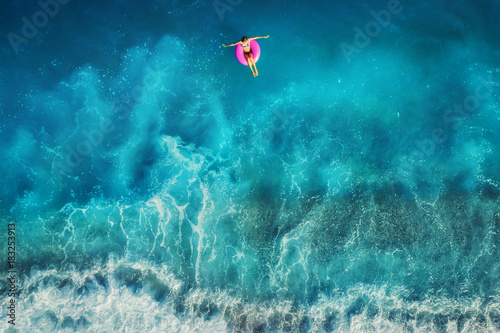 Aerial view of young woman swimming on the pink ring