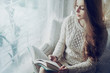 Young beautiful girl wearing knitted dress sitting on windowsill, holding and reading book. Day light. Christmas, New year, winter holidays concept. Copy space for text.