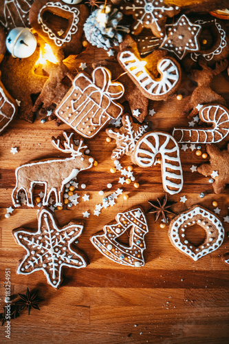 Sticker Freshly baked and homemade gingerbread cookies and food decorations on wooden table, flat lay view from above. Christmas handmade bakery. Family festive culinary and New Year traditions concept.