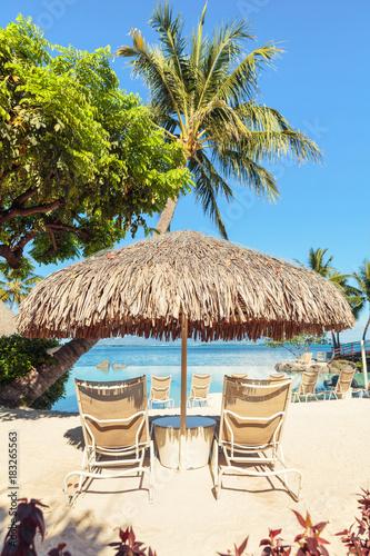 Two Sun-loungers and Tiki hut sun umbrella