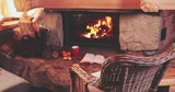 Warm Cozy Fireplace With Real Wood burning in it. Magical atmosphere. Cup of hot drink and book ready for evening relax. Cozy winter concept. Christmas and travel background with space for your text. - 183280757