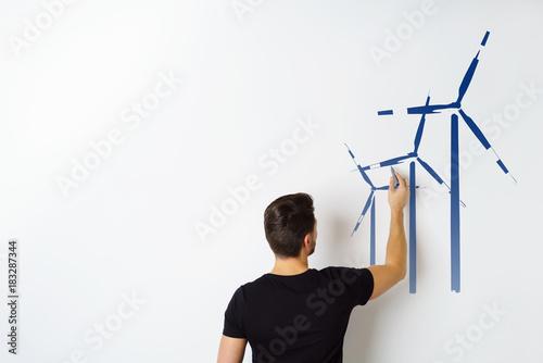 mann zeichnet windräder auf eine weiße wand Poster