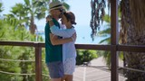 young happy loving pair is embracing and kissing on a balcony in tropical garden in sunny day - 183289749