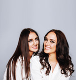 two sisters twins posing, making photo, dressed same white shirt - 183291398