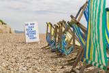 Deck chairs on the pebble beach in Beer, Devon, UK - 183295124