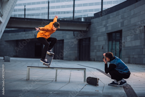 man taking photo of skateboarder doing trick over bench
