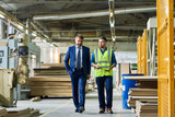 Full length portrait of young workman giving tour of modern factory to handsome mature businessman discussing possible investment, copy space - 183299746