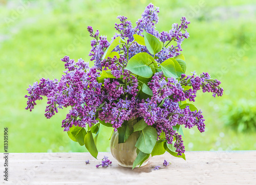 beautiful bouquet of purple lilac in vase outdoors