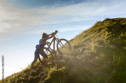Biker pushes bicycle up in the mountains
