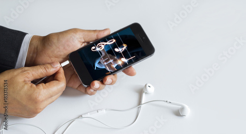 Fotobehang Muziek Hands insert earphone jack to smartphone with music on screen. All on screen are designed up.