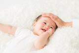 Fototapety 女性に撫でられる赤ちゃん(笑顔)