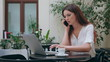 A beautiful girl speaking on the mobile phone in front of an open laptop in the room. Medium shot. Soft focus.