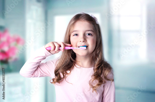 Caucasian child girl cleaning teeth in bathroom.
