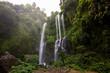 Woman in white dress at the Sekumpul waterfalls in jungles on Bali island, Indonesia - 183338356