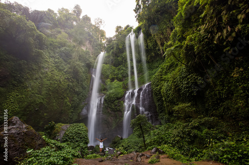 Woman in white dress at the Sekumpul waterfalls in jungles on Bali island, Indonesia - 183338356