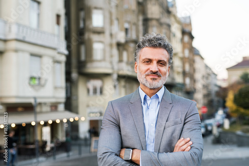 Wall mural Mature businessman with smartwatch in a city.