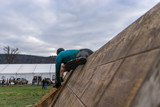 Athlete climbing over a wooden wall at an obstacle course race - 183352307