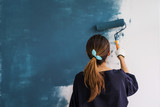 Young asian happy woman painting interior wall - 183353505