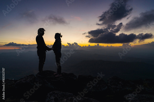 Silhouette of loving couple embracing on the mountain Poster