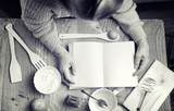 Recipe book in the hands of an elderly woman - 183356397