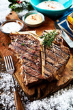 Close up view of grilled t-bone steak with sauces