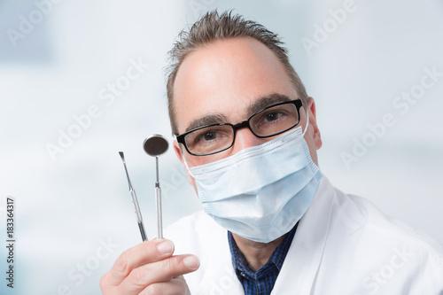 Fototapeta Zahnarzt mit Mundschutz und zwei Instrumenten