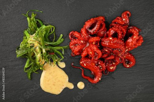 Fototapeta Seafood baby octopus and seaweed salad on black