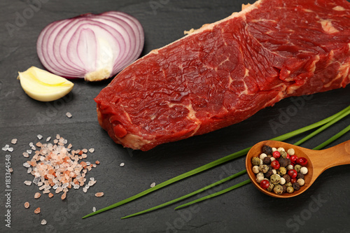 Fotobehang Steakhouse Raw beef steak meat cut and spices on black board